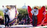 Mexican folklorico dancers at Fiesta with church dome in the background