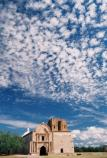 vertical image of church facade with clouds overhead