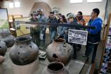 A group of students look at large earthenware pots.