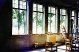 Interior view of the window sashes being removed for restoration. The walls are blackened due to a previous fire. The desks are not original to the school.