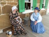 Two women in 19th century clothing on a porch.