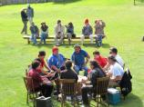 Ten drummers and singers sit around the large drum.