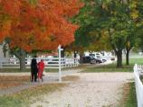 An elderly couple stolls down the historic Downey Trace boardwalk amid the autumn foliage and fallen leaves.