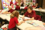 Volunteers lead quilting living history activity for students