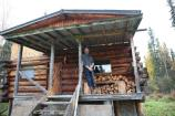 The Last Homesteader with bear protection in front of his cabin.