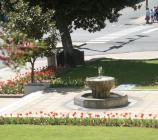 Beds with red tulips line the entrance to the park headquarters building, with a historic fountain spouting hot springs water in the middle.