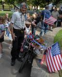 Older man with long gray braids is standing next to his bicycle on a sidewalk. His bicycle has an American flag fastened to the back of it and also one fastened to the basket in the front.