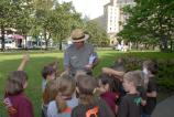 Ranger in Corps of Engineers uniform is slightly bent forward handing small items to school children in front of him.