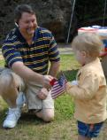 Dark haird man on his haunches with blond child in yellow dress who is holding an American flag.