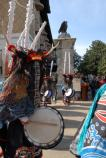 Closeup side view of Deer Dancer with others in background. Costume includes long dark haired wig that hangs in front of face so that face is not seen; headdress that is long white wrapped vertical pieces representing antlers; black, red and blue outfit with white socks and sandals. Dancer is holding a drum