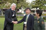 Close in shot of Andrew Jackson reenactor on left shaking hands with Mayor Oishi, center, and Supt. Fernandez dressed in uniform polar fleece jacket. The green lawn grass and trees are in the background.