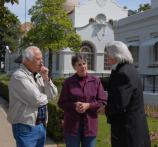 President Andrew Jackson reenactor stands on right, talking to visitors, a man in an off white zip front jacket and a woman in a burgandy colored jacket. They are standing on the sidewalk with the Quapaw Bathhouse in the background.