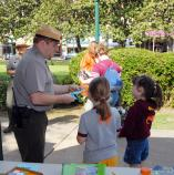 There is a table in the foreground. The male Park Ranger is handing a blue paper to two children. There are two women and another park ranger on the sidewalk in the background.