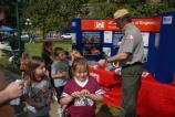 Corps of Engineers Ranger stands in front of information booth, handing small packets to children. The booth has a table with a bright red covering and a bright blue and red exhibit on the table.