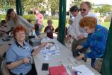 Female red headed postal worker smiles and holds up a commemorative cachet. On other side of table, people are looking at the cachet.