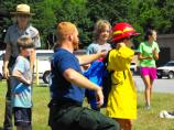 Firefighter assists child with wildland fire gear