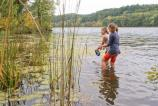 Two young girls holding small fishing nets wade in the water near cattails