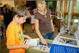 a youth and an adult stand next to an exhibit looking for an artifact that matches their Scavenger List