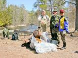 Two volunteers are showing a uniformed ranger the garbage: rusty metal and plastic bags of smaller garbage