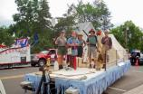 people are dressed as a logger, a fur trader, camper, and rangers on a flat bed with tent