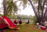 At left, a dome tent; at right is a picnic table with camping gear.  At center, three people sit looking at the river.