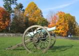 Cannon with fall colors in the National Cemetery in the background.