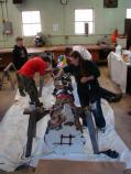 Scouts help the NPS and artist Erin Aylor paint the new totem pole.