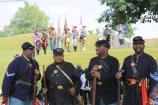 Four men portray U.S. Colored Troops in foreground, in background a Confederate color guard stands on a slope.