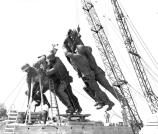 Grouping of three bronze statues being lifted onto the memorial's base with a crane