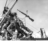 Six men observe as a bronze rifle is lifted into place with a crane