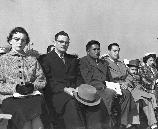 Three men in civilian clothes sit in front of a crowd