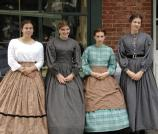 Living history ladies pause for a picture in front of the Dry Goods Store.