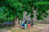 A group of visitors listening to a living history interpreter under a tree