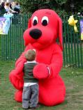 An egg roller is getting a hug from Clifford the Big Red Dog