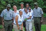 YCC members and staff pose for a group shot outside in the park gardens.