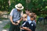 A ranger shows visitors how to use a GPS unit.