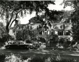 Photograph of the front of the Old House with a vintage car parked in front, C. 1950s.