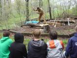 Costumed ranger demonstrating log hewing for school group