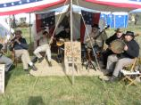 Several reenactors playing flute, fiddle, guitar, banjos and a large tambourine