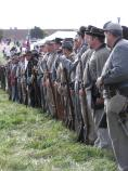 A line of Confederate troops, nearly all clad in gray, in line and receiving instructions.