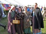 Four young women reenactors in camp. Their smiles seem to defy the hardships of camp life.