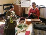 Two living history interpreters in period attire sit and work in one of the house's chambers (bedrooms).