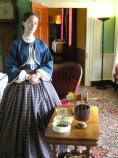 A living history interpreter in Civil War era attire, present to describe part of daily life in the plantation house.