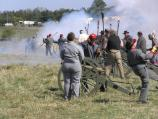 Confederate artillery soldiers stand amid the smoke of their just-fired cannon.