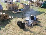 A campfire smoking beneath a sooty iron grill and well-worn pots and kettles. In the background, a reenactor catches a nap while stretched out on several wooden boxes