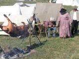 A few reenactors in camp. One cleans his firearm, two stroll by, and a roast pig dinner slowly cooks on a large spit over a campfire.