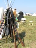 In the foreground stands a cone of stacked percussion-cap long guns, their bayonets interlocked forming the cone top. Two reenactors stand in the near background, a row of tents to their left