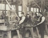 Workers operating machine for Edison storage battery production.