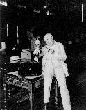 Thomas Edison looking at his motion picture projector made for the home.