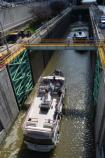 A modern canal boat entering a steel and concrete canal lock.